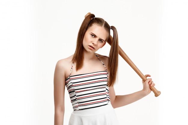 Молодая милая девушка представляя при летучая мышь, изолированная на белой стене