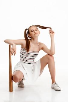 Молодая милая девушка представляя с летучей мышью над белой стеной
