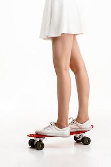 Молодая красивая девушка, скейтбординг на белой стене закройте.