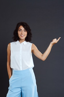 Красивая молодая женщина, стоя над серой стеной и указывая пальцем