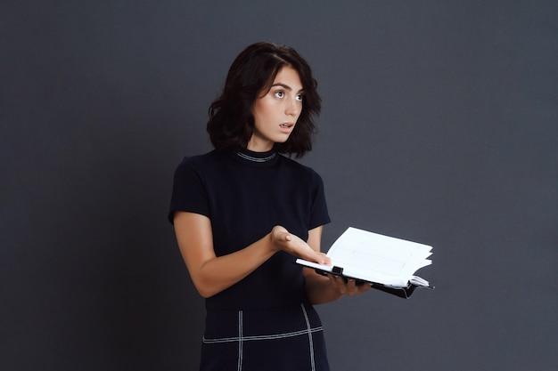 ノートブックを手で保持している混乱している若い女性