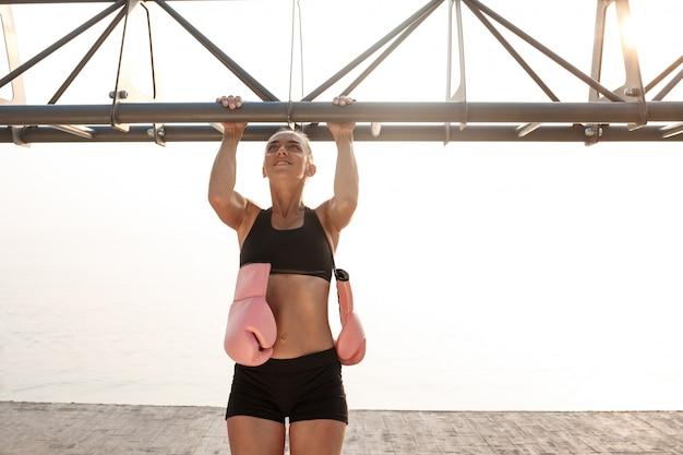 海辺でボクシングのトレーニングの準備をしている陽気な美しい少女の肖像画。