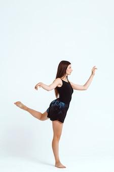 白い壁にポーズをとって若い美しいコンテンポラリーダンサー。コピースペース。