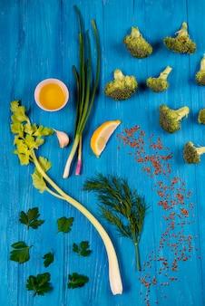 パセリ、フェンネル、セロリ、レモン、ブロッコリー、ブルーの木製テーブル