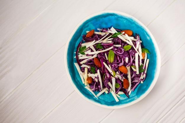 白い木製の表面上の新鮮な野菜とグリーンサラダ