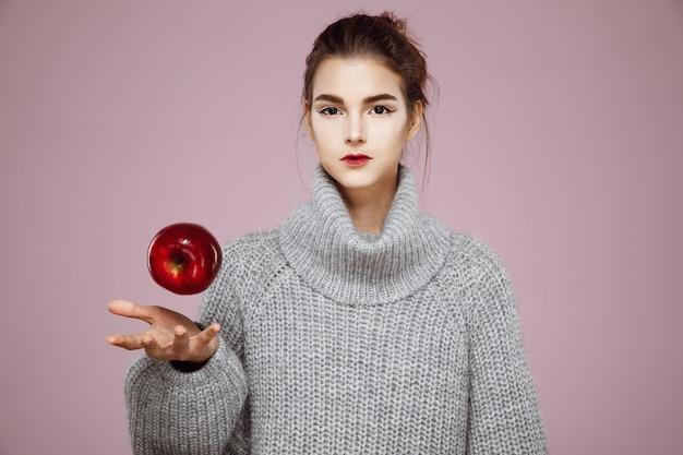 Женщина подбрасывает красное яблоко на розовый