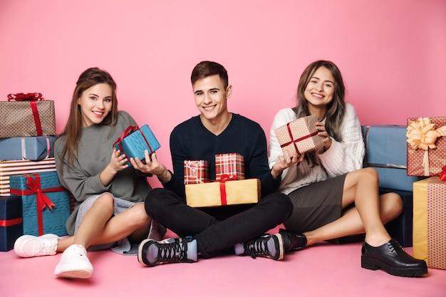 Юные друзья сидят среди рождественских подарочных коробок на розовом