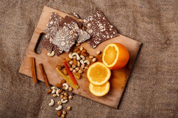 チョコレートオレンジシナモンと木製の机の上のナッツ。