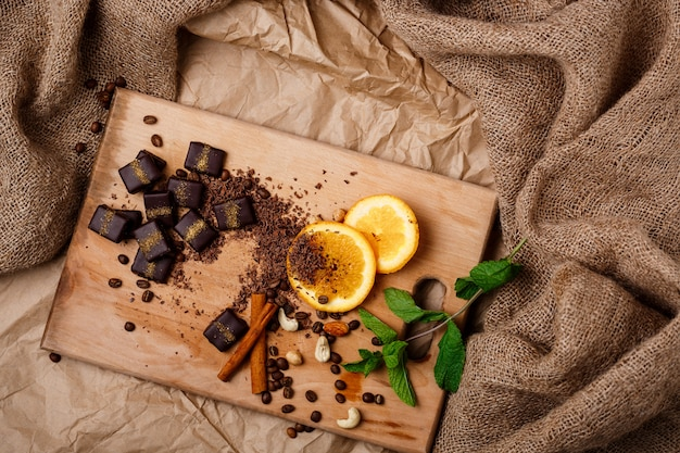 木製の机の上のチョコレート菓子オレンジミントシナモンとナッツ。