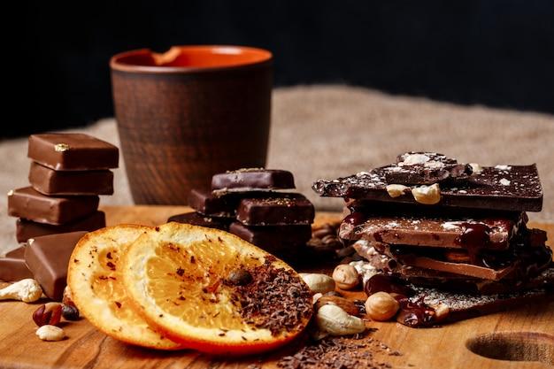 木製の机の上のチョコレートキャンディーオレンジシナモンとナッツ。