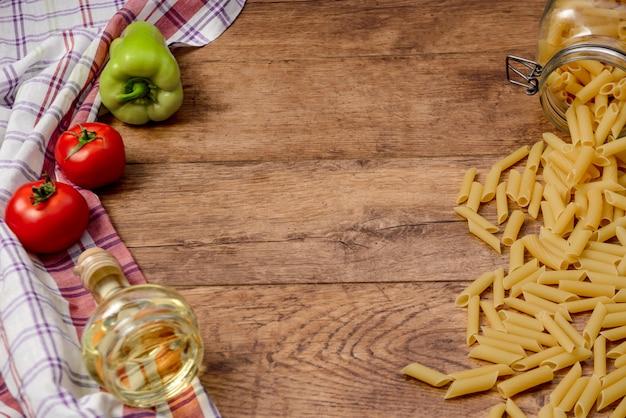 マカロニ、トマト、パプリカ、パスタを調理する準備ができての木製のテーブルのオイル