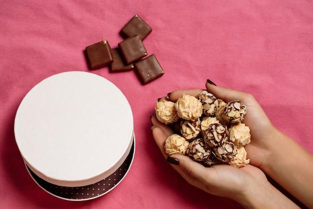 Шоколадные конфеты в женских руках на розовом