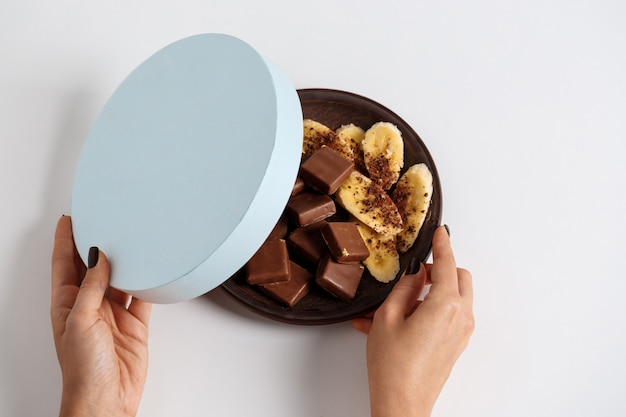 Женские руки открывают коробку с шоколадом и бананом на белом