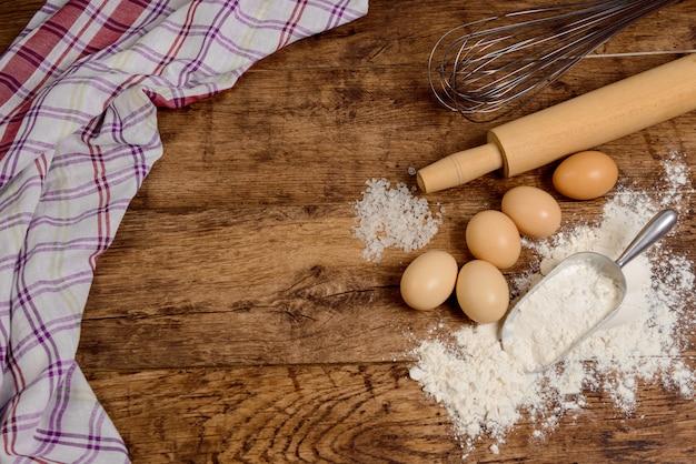 Мука, яйца, соль, полотенце, скалка на деревянном столе, готовые для приготовления пищи