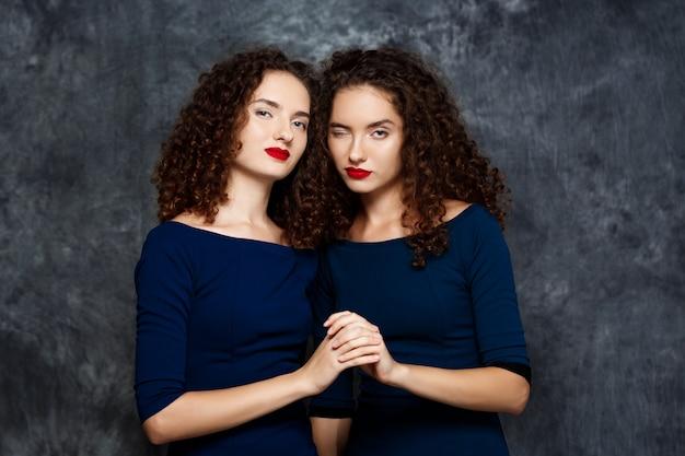 グレーでウインク笑顔双子の姉妹