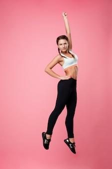 ピンクに分離された楽しい作るジャンプアップスポーティな女性