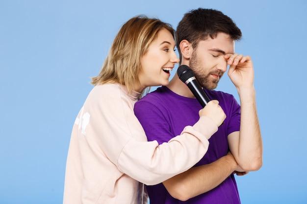 Красивая пара над синей стеной. девушка поет в микрофон мужчине недовольно.
