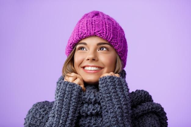 ニット帽子と紫の側を見て笑っているセーターの若い美しい金髪の女性。