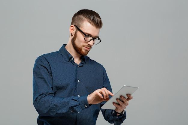 灰色の壁の上にタブレットを見て若い成功した実業家。