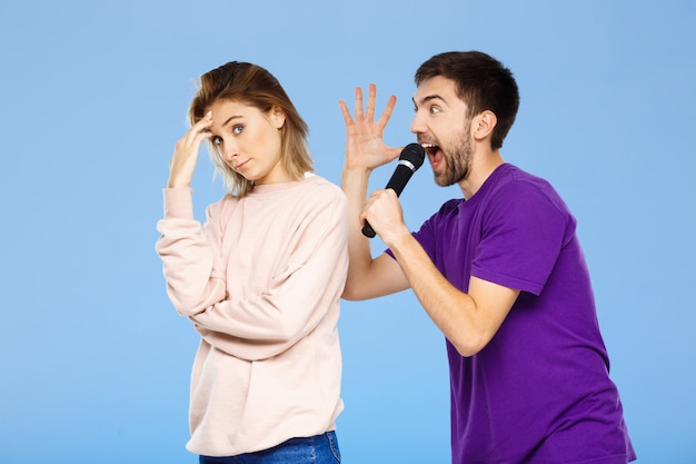 Красивая пара над синей стеной человек поет в микрофон девушка недовольна.