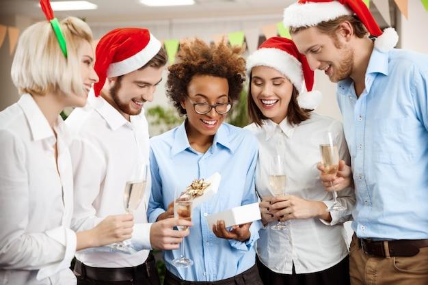 プレゼントを与えて笑顔のオフィスでクリスマスパーティーを祝っている同僚。