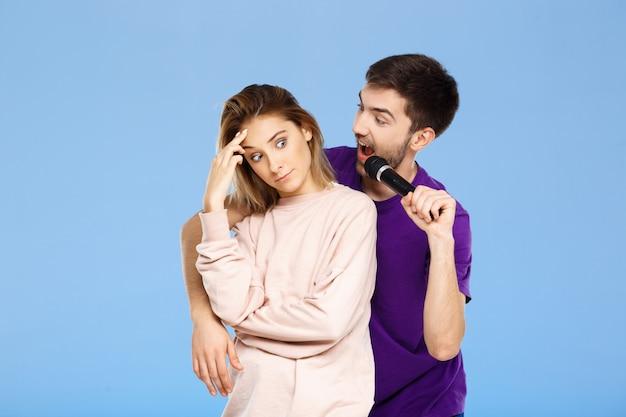 Красивая пара над синей стеной. мужчина поет в микрофон девушке порадовал.