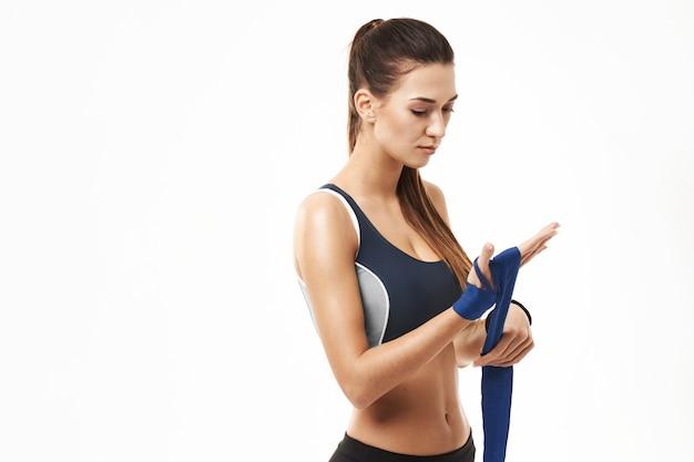 Фитнес спортивная женщина намотки эластичной повязкой в наличии на белом.