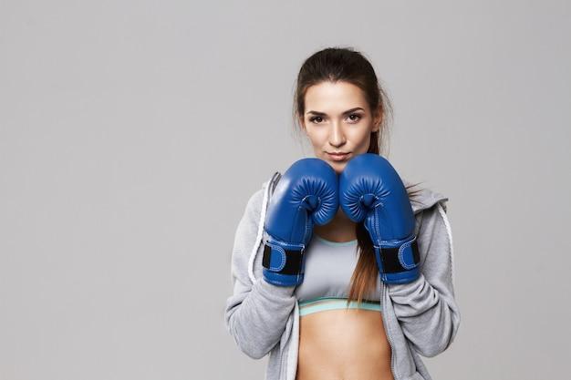 白のトレーニング青いボックス手袋を身に着けている陽気な女性。