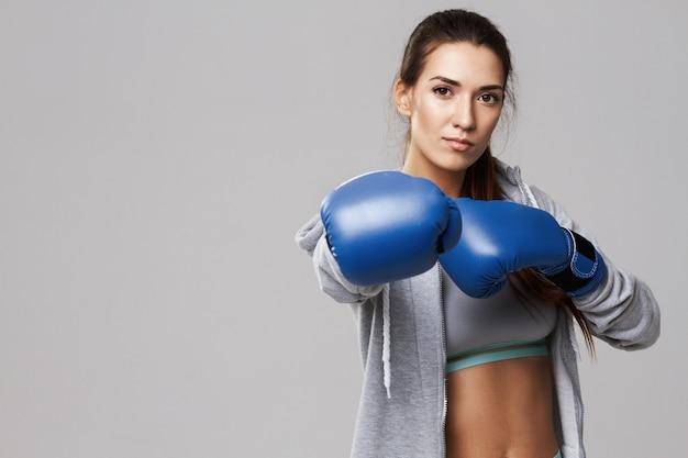 Спортивная женщина, одетая синий боксерские перчатки обучение на белом.