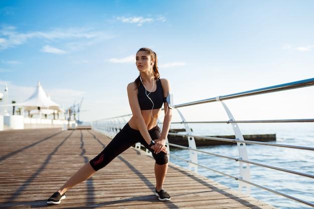 壁に海の海岸でスポーツ演習を行う若いフィットネス女の子