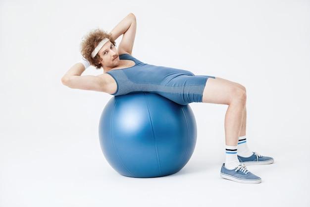 Парень в синем комбинезоне работает на мышцы живота