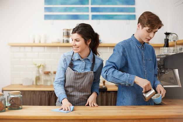 幸せそうに笑ってテーブルを拭く女性バリスタ。注ぐコーヒーを作る。