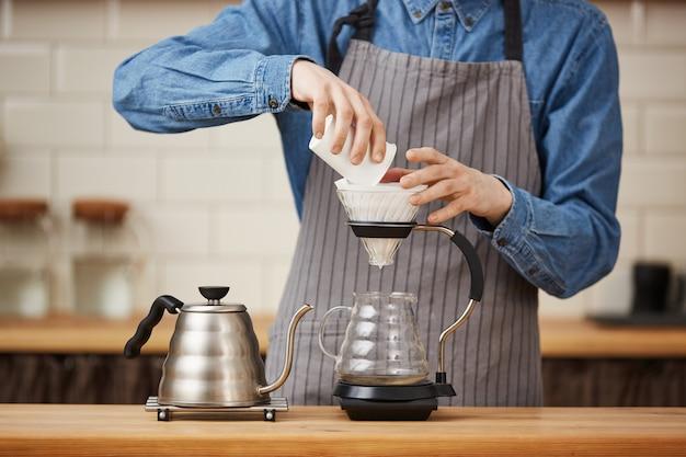 男性のバリスタが地面のコーヒーを作る注ぎ口を注ぐのクローズアップ。