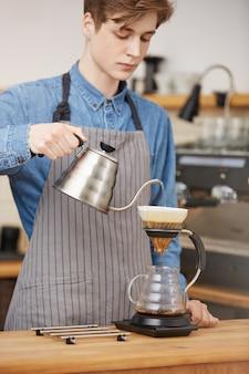 Мужской бариста льёт воду через гущу кофе.