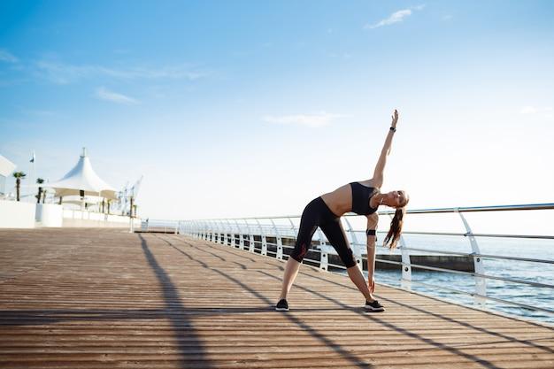 Молодая фитнес-девушка делает спортивные упражнения у моря