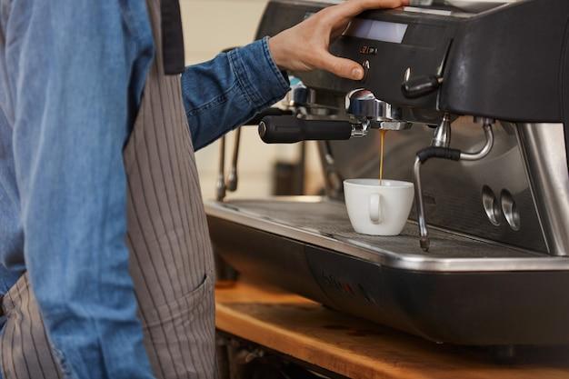 プロのコーヒーマシン。コーヒーを飲むバーテンダーのクローズアップ。