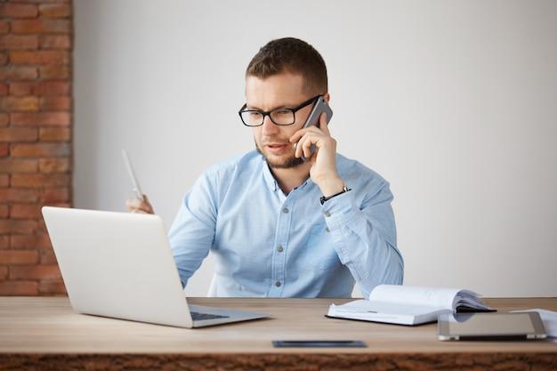 メガネと会社のオフィスに座っている青いシャツの若い深刻な財務マネージャー