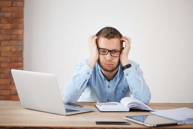 Портрет директора молодой компании в очках, держа голову руками, глядя в сторону с усталым и несчастным выражением лица, измученный после тяжелого рабочего дня.