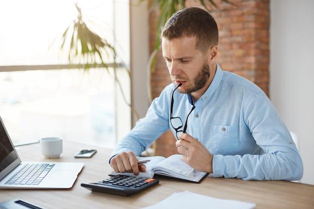 深刻な財務マネージャーがオフィスで朝を過ごす、メガネを口の中で保持している、計算結果を見てのクローズアップ