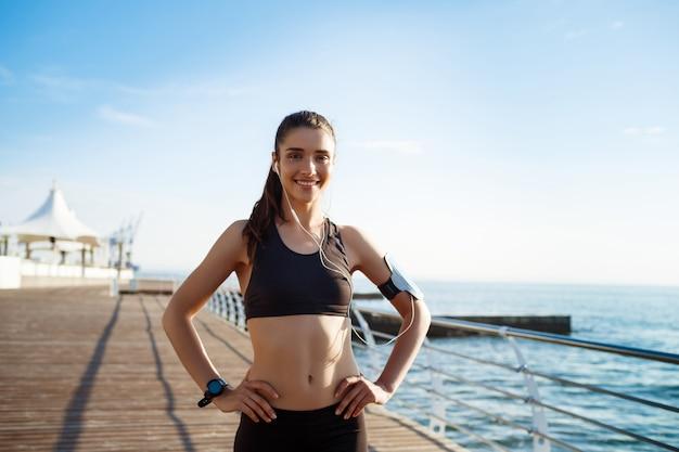 海沿いのスポーツ演習の準備ができて若いフィットネス女の子