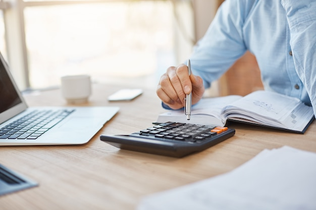 Закройте деталь профессионального серьезного бухгалтера, сидящего в светлом офисе, проверяющего прибыль финансов компании на калькуляторе