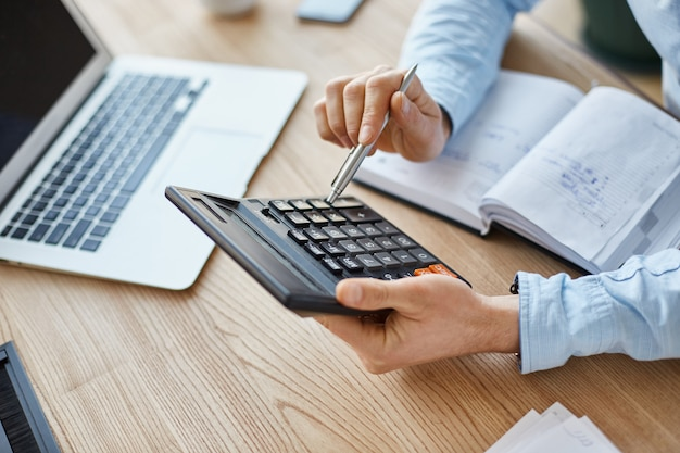 プロの深刻なファイナンスマネージャーのビューのトリミング、計算機を手に持って、会社の月の利益をチェック