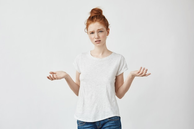 若い不機嫌な赤毛の女性が身振りで示す混乱している女性がボーイフレンドと主張しています。白い。