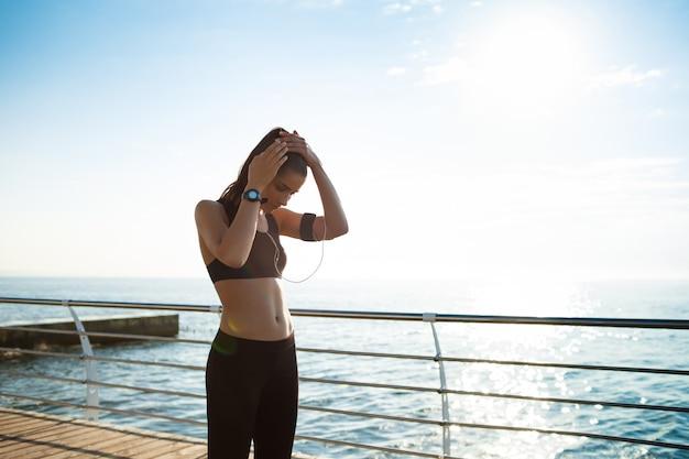 Молодая фитнес-девушка готова к занятиям спортом у моря