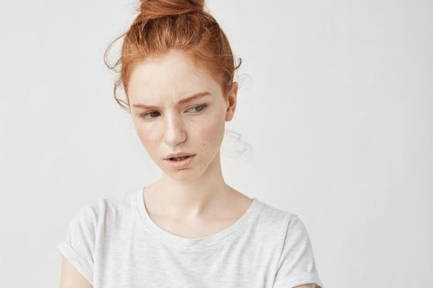 そばかすのある不満の赤毛の女性の肖像画。