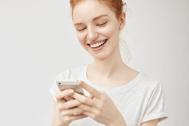 Молодая рыжая женщина улыбается, отправляя смс с фотографиями в социальных сетях с улыбкой