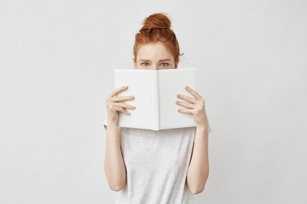 ノートブックの後ろに顔を恐ろしく隠して赤毛の女性。