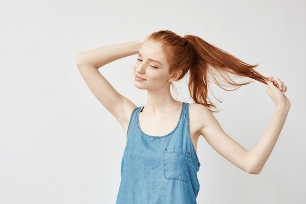 若い赤毛の女性は彼女の散髪を修正します。
