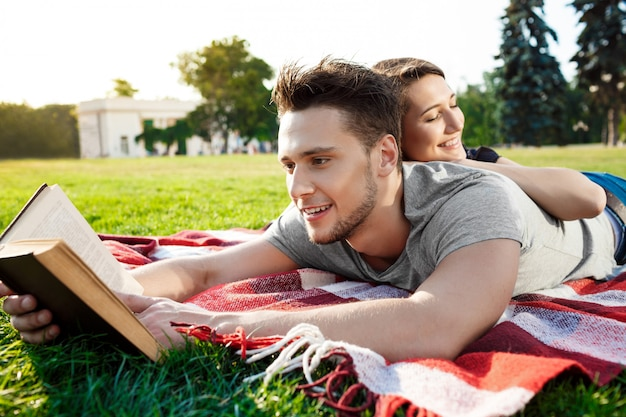 Чтение молодых красивых пар усмехаясь на парке.
