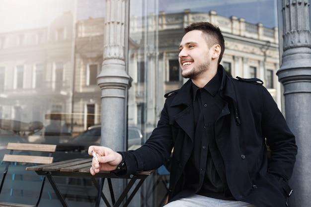Молодой веселый человек курить сигарета, весело улыбаясь, глядя в сторону.